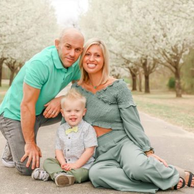 Meghan Newell Davis with her husband, Kenneth, and son, Austin. They are dressed up and posing outside on a pathway between trees with white blossoms.