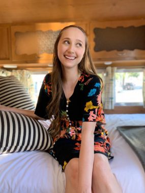 young adults with scleroderma / Scleroderma News / Samantha Showers sitting on a bed in a vintage RV
